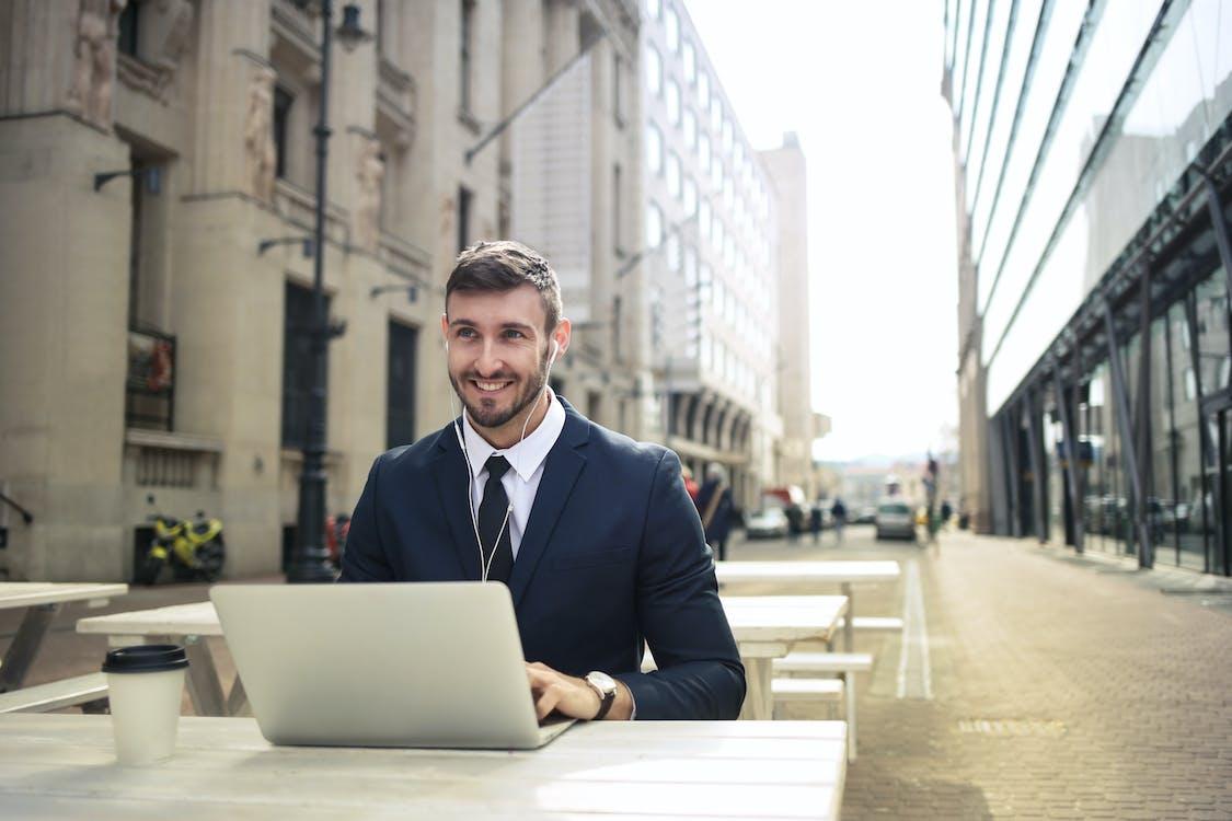 Man in Black Suit Jacket Using Macbook
