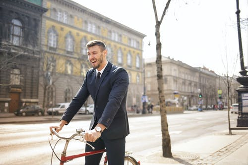 Man in Black Suit Jacket and Black Pants While Riding a Red Bicycle