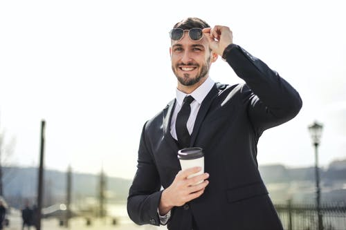Man in Black Suit Holding White Cup