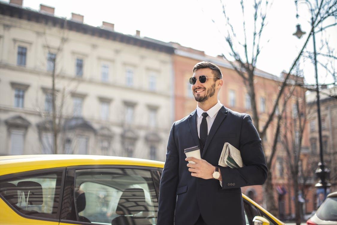 Man in Black Suit Standing Beside Yellow Car