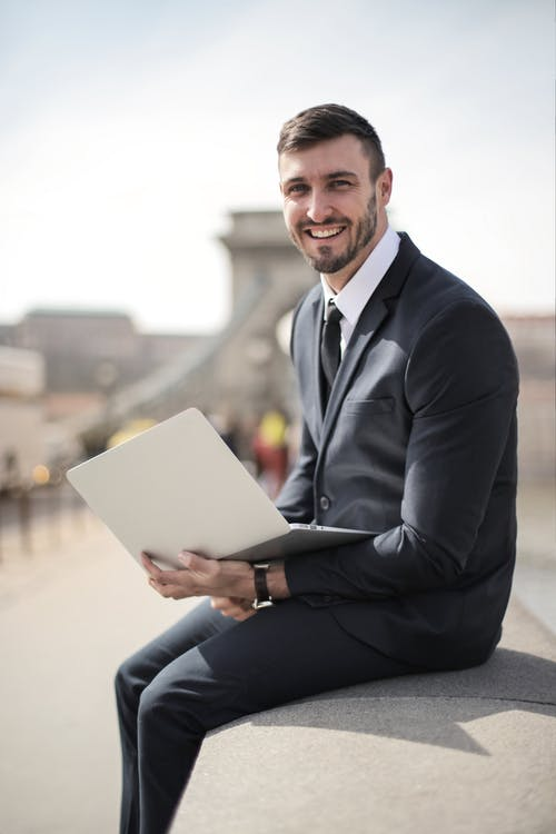 Man in Black Suit Jacket Holding Silver Laptop Computer