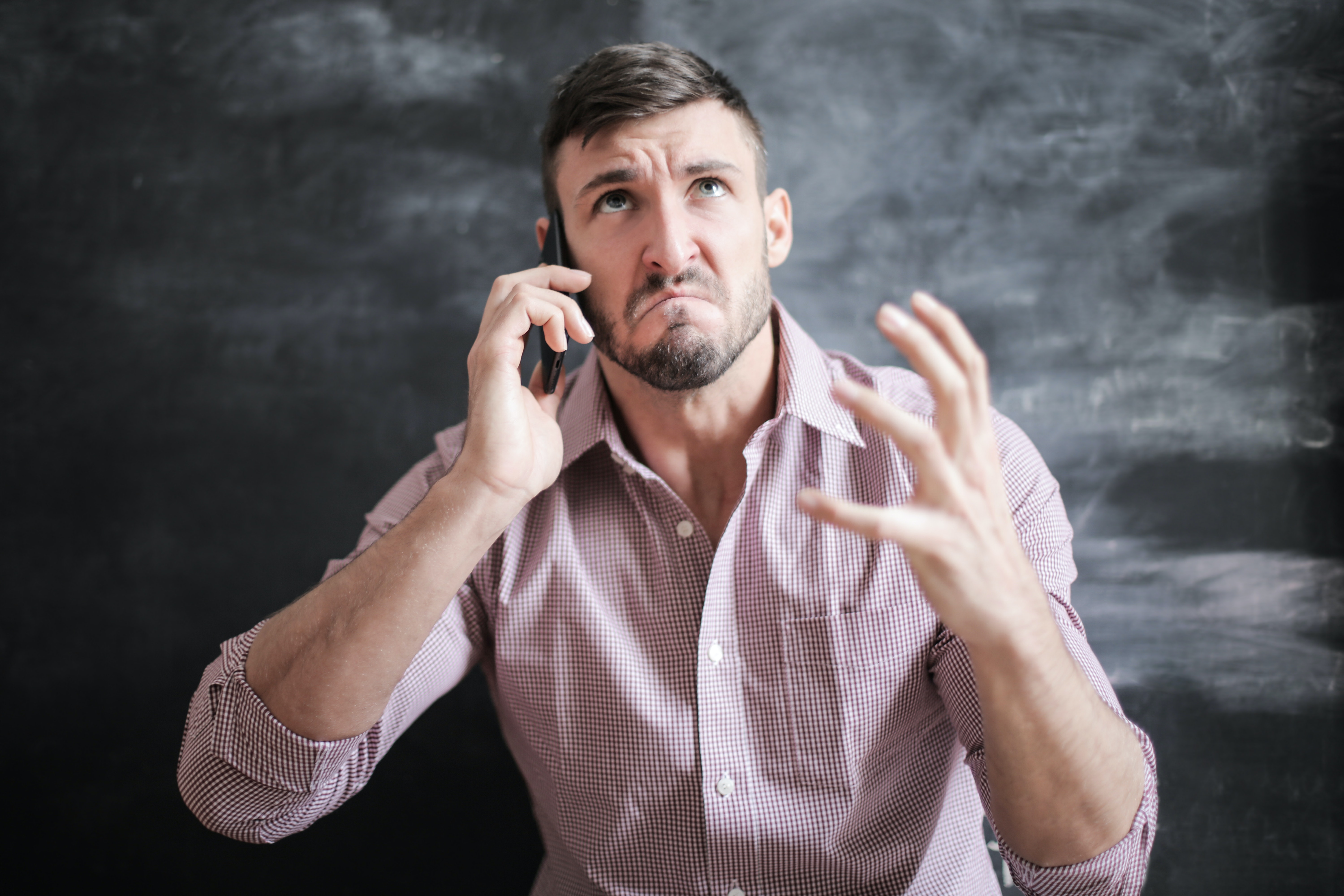 Angry man using a mobile phone. | Photo: Pexels