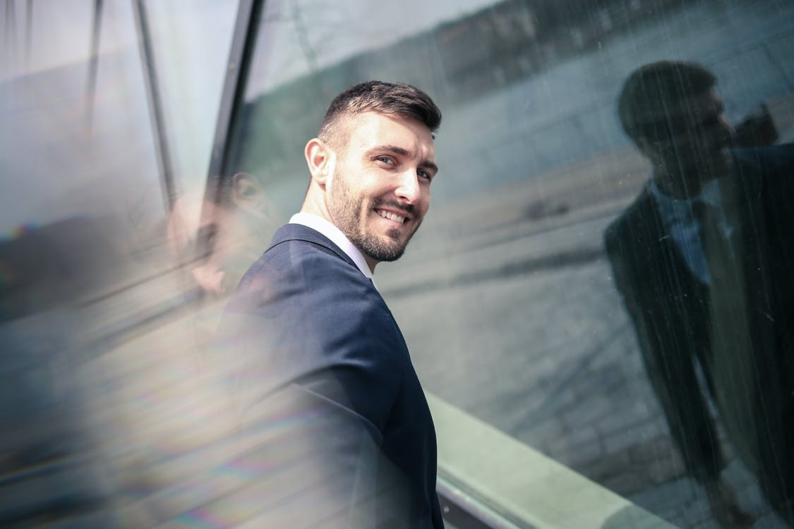 Cheerful businessman in formal wear standing in front of glass wall