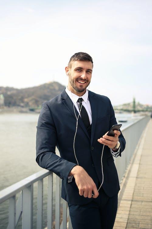 Homem De Paletó Preto Segurando Um Smartphone Preto