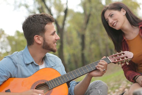 Photo of Man Playing Guitar Beside a Woman