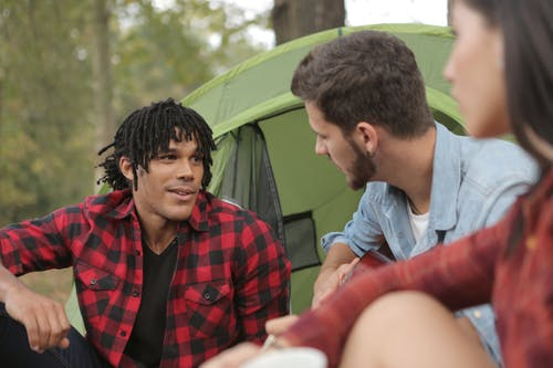Multiethnic young people talking at campsite