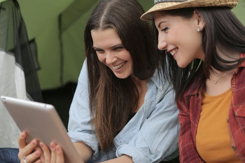 Photo of Women Smiling While Looking at Ipad