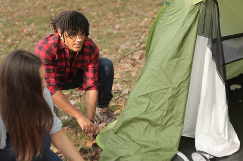 Diverse man and woman pitching tent
