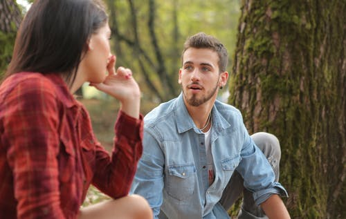 Man in Blue Denim Button Up Shirt Sitting Beside Woman Near Tree