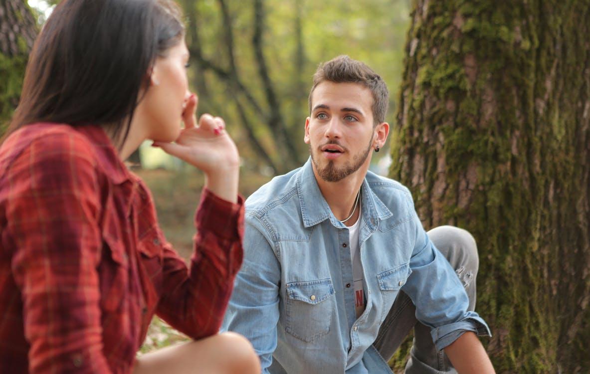 Man in Blue Denim Button Up Shirt Sitting Beside Woman Near Tree