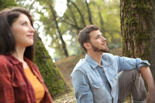 Pensive man in denim and blurred woman in red shirt sitting on ground in forest and looking away