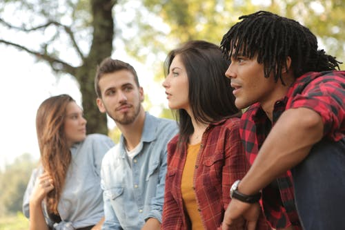 Multiracial young people sitting in green forest