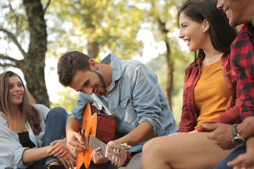 Friends spending time together with a guitar. | Photo: Pexels
