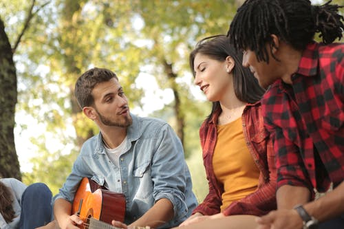Denim dressed man playing guitar and singing while sitting with friends in park