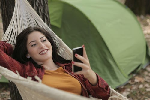 Photo of Woman Lying on Hammock While Using Cellphone