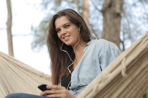 Mulher Sentada Na Rede Enquanto Ouve Música