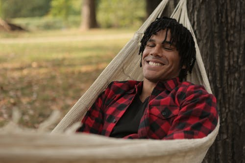 Man Lying on Hammock While Smiling