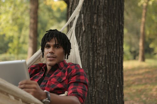 Man in Red Plaid Shirt While Lying on Hammock