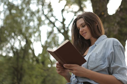 Woman Holding and Reading Brown Book