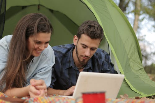 Young couple browsing netbook at campsite