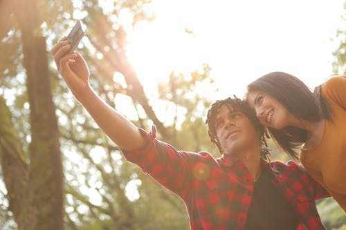 Photo of Man and Woman Taking Selfie Using Smartphone