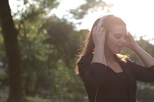 Woman Wearing Black Jacket While Listening to Music
