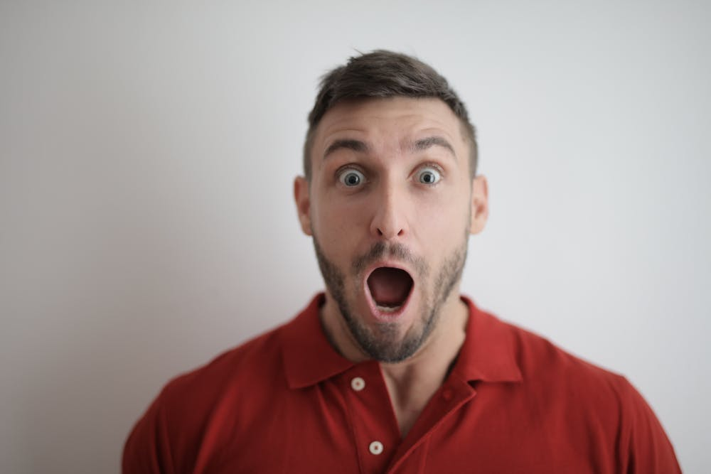 Shocked face of a man in red button up shirt. | Photo: Pexels