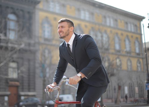 Man in Black Suit Jacket and Black Pants Riding on Red Bicycle