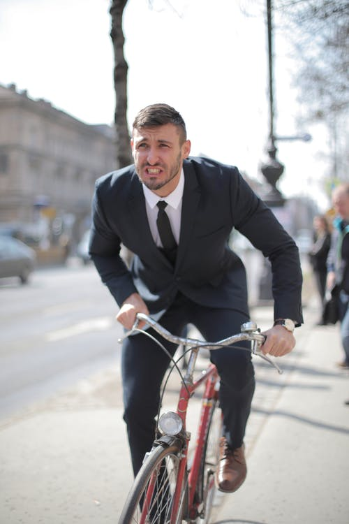 Man in Black Suit Jacket Riding Red Bicycle on Road
