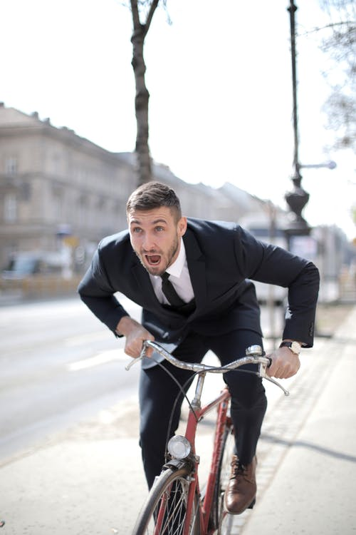 Man in Black Suit Jacket Riding Red Bicycle