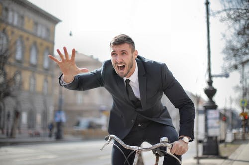 Человек в черном костюме на велосипеде