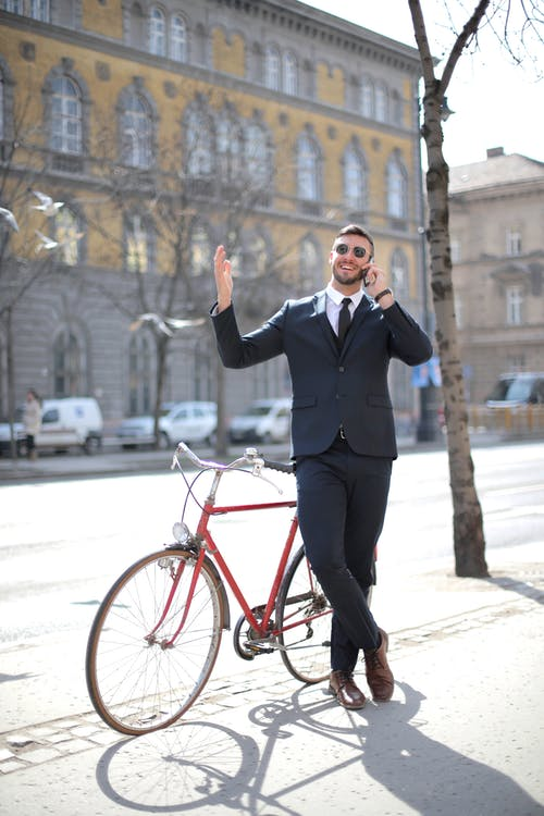 Man in Black Suit Jacket and Black Pants Standing Beside Red Bicycle