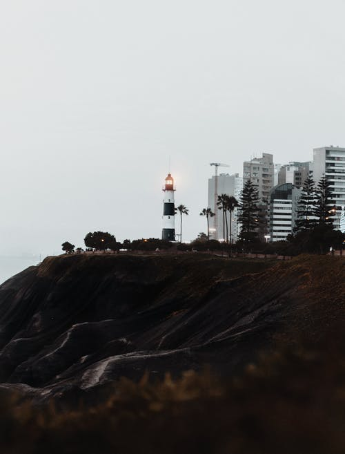 White and Black Lighthouse Near Cliff