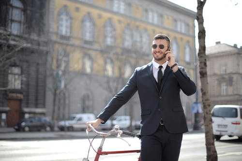 Man in Black Suit Jacket and Black Dress Pants Holding Red Bicycle