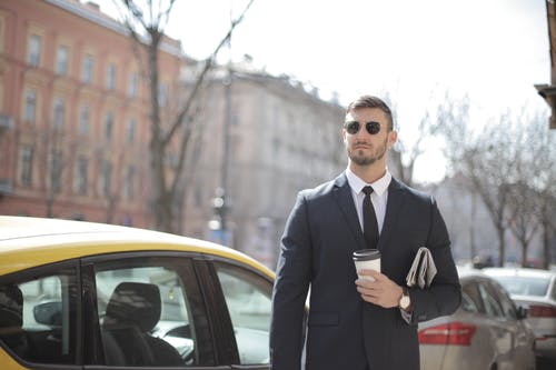 Man in Black Suit Standing Beside Yellow Car