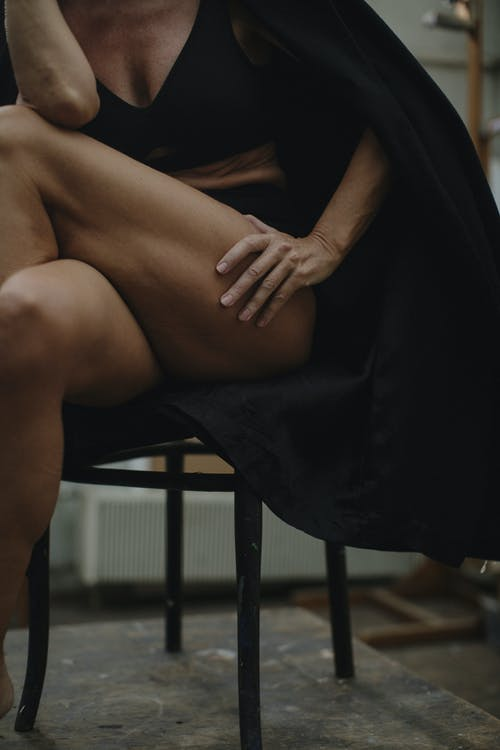Woman in Black Dress Sitting on Black Chair