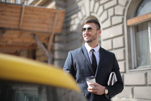 Man In Black Suit Holding A Cup Of Coffee