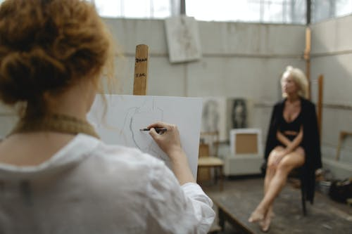 Woman Sketching on White Cardboard
