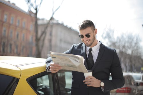 Homme En Costume Noir Tenant Un Journal