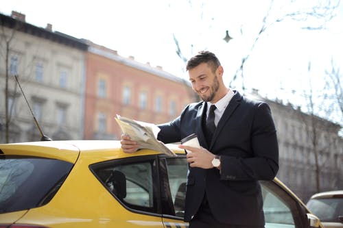 Man In Black Suit Holding Newspaper