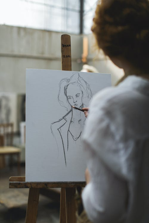 Woman in White Shirt Sketching on Paper