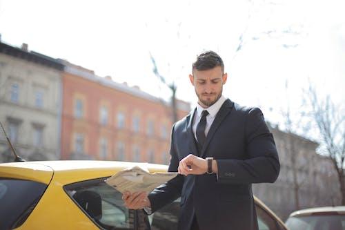 노란 차 옆에 서있는 검은 양복에 남자