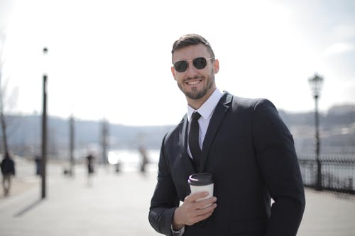 Man in Black Suit Holding Coffee Cup