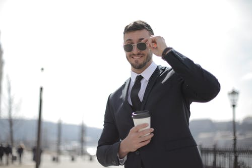 Man In Black Suit Holding A White Cup