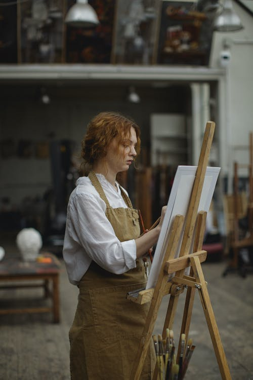 Woman in White Long Sleeve Shirt and Brown Apron Standing while Drawing
