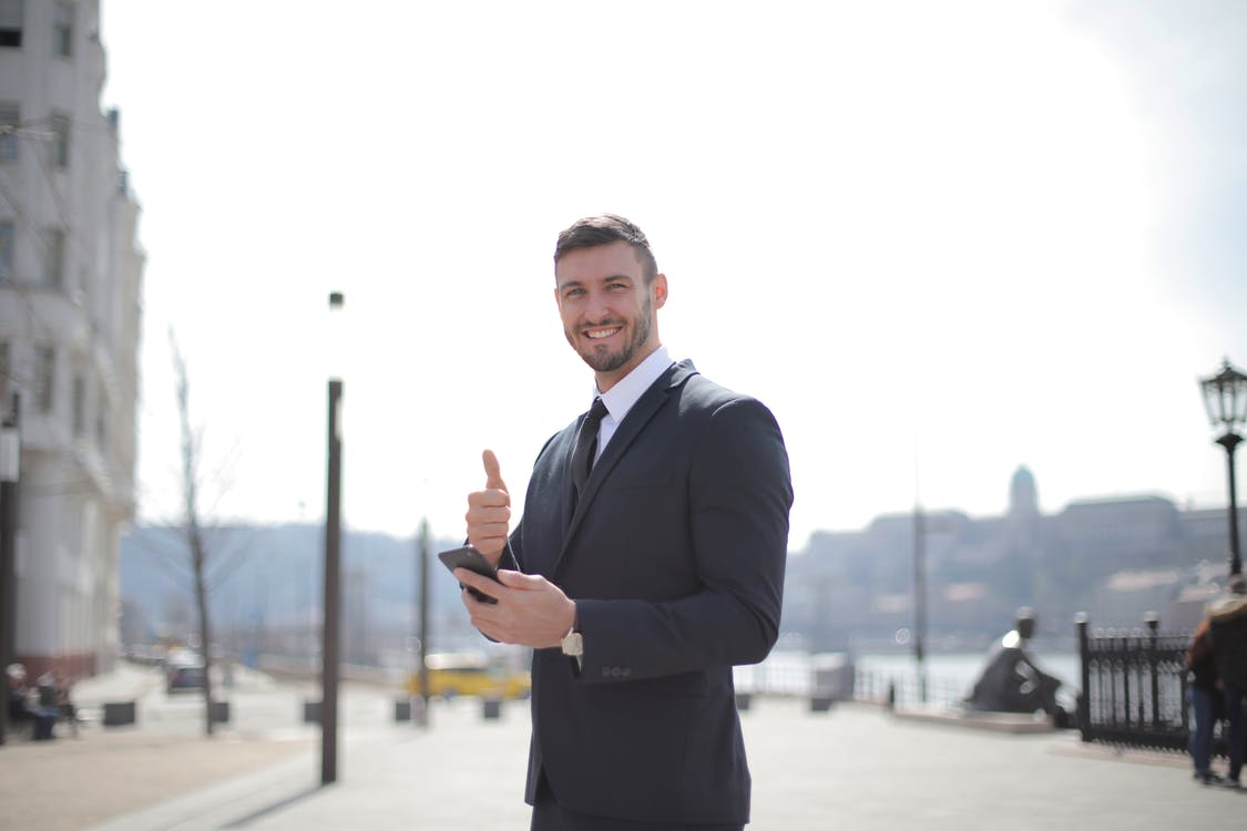 Man in Black Suit Jacket While Holding a Smartphone