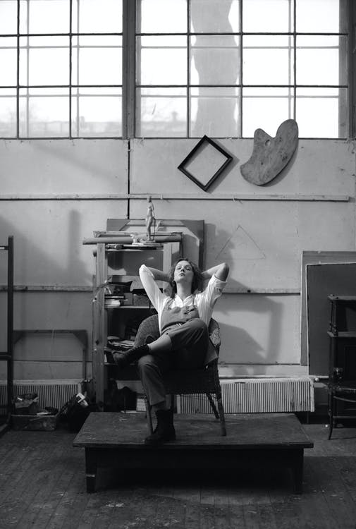 Grayscale Photo of a Woman Resting on a Wooden Chair