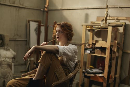 Frau Im Weißen Langarm Sitzt Auf Braunem Stuhl