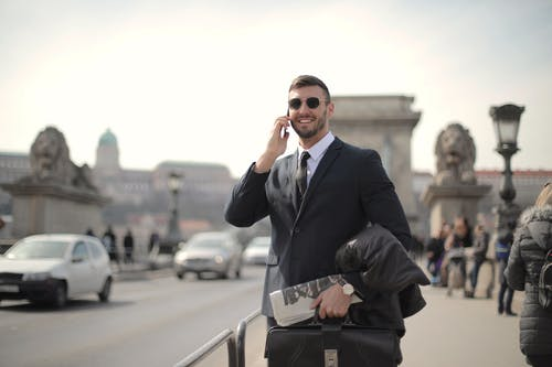 Man in Black Suit Jacket and Black Sunglasses While Using Smartphone