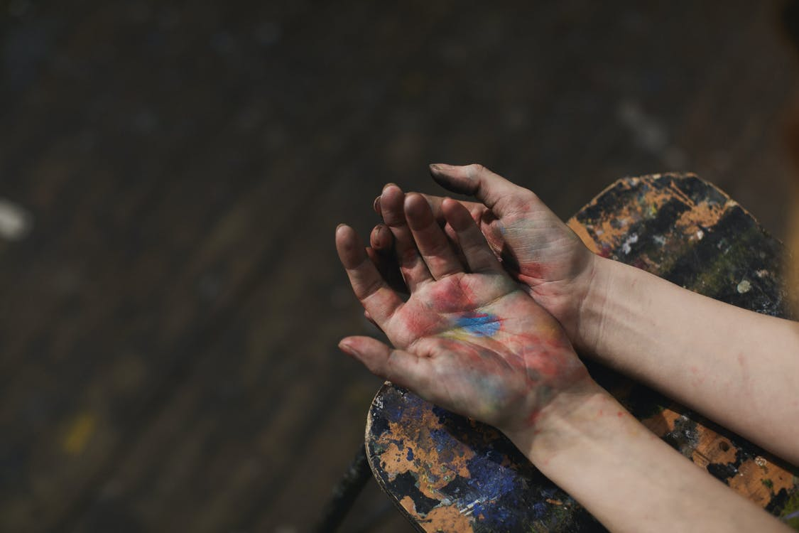 Person With Blue Green and Red Paint on Hand